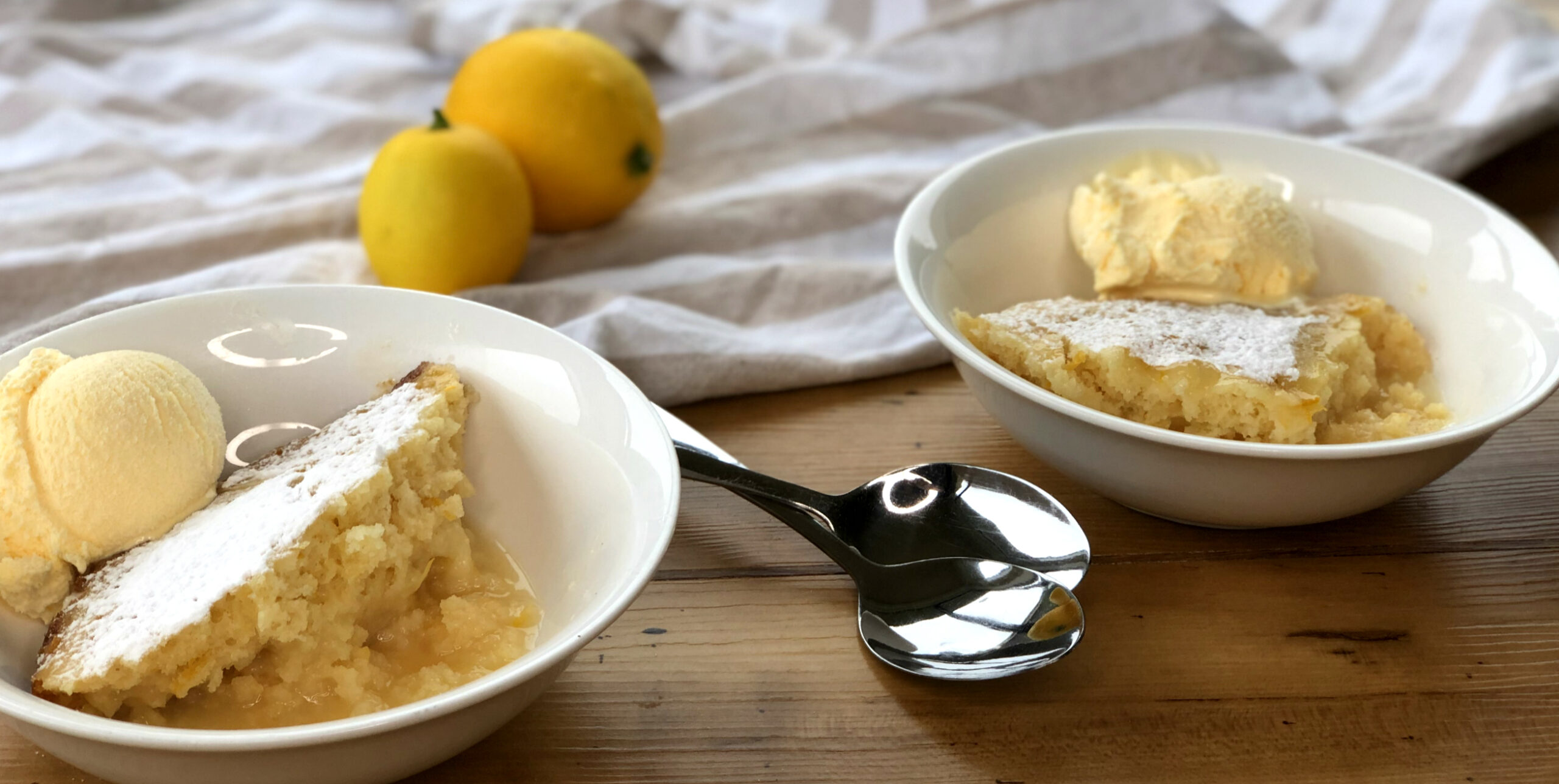 Warm lemon slow cooker desserts in two bowls with ice cream and two lemons as props